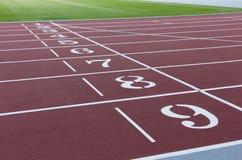 跑的红色体育轨道在体育场 连续健康生活方式概念 炫耀背景摘要纹理 免版税库存照片