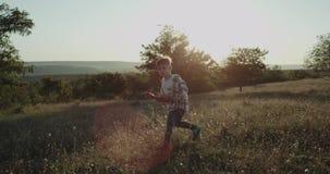 跑的逗人喜爱的男孩通过在自然,好日子,使用与飞机的小男孩中间的草 股票录像