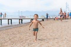 跑路的愉快的男婴在海边附近 免版税图库摄影