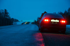 黑跑车在雨中在晚上 库存照片