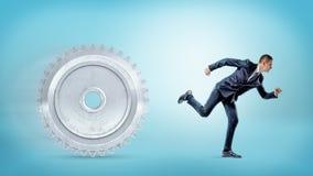 跑远离在蓝色背景的一个大金属正齿轮的商人 免版税库存照片