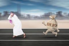 跑远离债务的阿拉伯人 库存照片