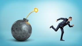 跑远离带有一根被点燃的保险丝的一个巨型炸弹的蓝色背景的一个小商人 库存照片