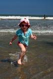 跑远离波浪的逗人喜爱的小女孩在巴厘岛海滩,库塔 免版税库存图片
