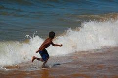 跑远离波浪 库存照片