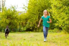 跑远离狗或短毛猎犬的女孩在夏天 图库摄影
