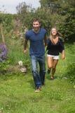 跑逗人喜爱的夫妇握手 免版税图库摄影
