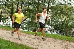 跑通过公园的两位人运动员 库存照片