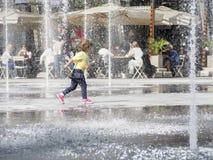 跑通过喷泉的孩子 免版税库存图片