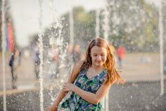 跑通过喷泉的愉快的矮小的小孩女孩获得乐趣 免版税图库摄影