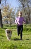 跑与您的狗的女孩 库存照片