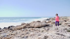 跑通过沿海洋的岩石足迹的年轻坚强的适合的白种人妇女 强风和波浪 t 影视素材
