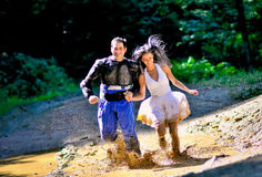 跑通过泥的夫妇 库存图片