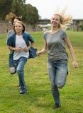 跑通过绿色草坪的少年在夏天在公园 库存照片