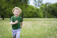 跑通过草的愉快的年轻男孩 免版税库存图片