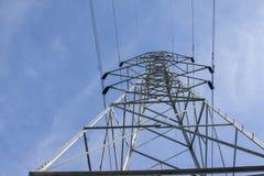 跑通过领域的电塔 免版税库存照片