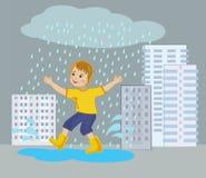 跑通过水坑的愉快的男孩在城市 库存照片