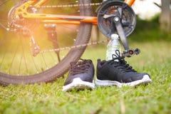 黑跑鞋和瓶在自行车车轮前面的水在绿草 免版税库存照片