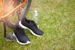 黑跑鞋和瓶在自行车车轮旁边的水在绿草 免版税图库摄影