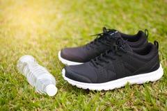 黑跑鞋和瓶在绿草的水 免版税库存图片