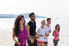跑,年轻体育赛跑者混合种族跑步在海滩制定出微笑的人愉快,适合的男性和女性 免版税库存照片