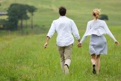 跑绿色领域的夫妇 免版税库存图片