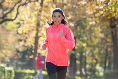 跑a的秋天运动服的可爱和愉快的赛跑者妇女 免版税库存照片