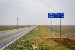 距离的路路标到市Yashkul 13和埃利斯塔在俄语的110 km 免版税库存照片