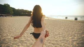 跟我学射击了跑和握在海滩的比基尼泳装的年轻性感的女孩人手在日落 免版税库存图片