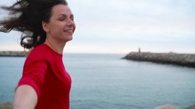 跟我学-拉扯人` s手手拉手走对在海滩的灯塔在的红色礼服的愉快的少妇 股票录像