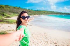 跟我学POV -在获得的爱的夫妇乐趣 在握在白色狂放的海滩的女朋友之后的笑的男朋友手和 图库摄影