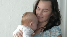 跟踪投入婴孩的母亲睡觉,当走时 可爱的妇女在手和步行上的抱着婴孩横跨客厅 库存图片