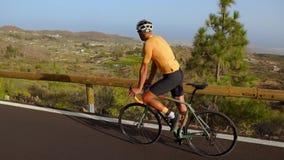 跟踪爬上山路的一个男性骑自行车者的录影射击 供以人员做在一条多小山高速公路路的循环的训练  影视素材