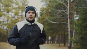 跟踪英俊的赛跑者人射击跑步的耳机的,当听的音乐在冬天早晨时停放 影视素材