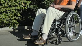 跟踪走与一个wheelchaired人的一个好人的射击 股票视频