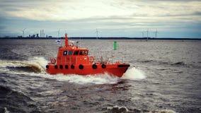 跟随为助理的橙色领航船对货轮 船驾驶术  免版税库存照片
