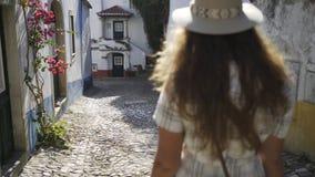 跟随从在街道Obidos上的后面妇女 股票录像