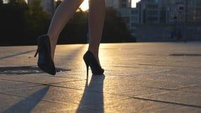 跟随到在走沿在日落时间的城市街道的高跟鞋鞋子的女性腿 女商人的脚上流的 股票视频