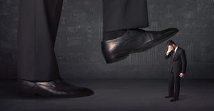 跨步在一个微小的businnessman概念的巨大的腿 免版税库存图片