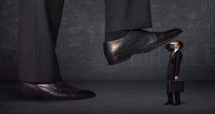 跨步在一个微小的businnessman概念的巨大的腿 图库摄影