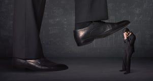 跨步在一个微小的businnessman概念的巨大的腿 库存照片