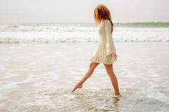 跨步在波浪的青少年的女孩 库存照片