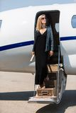跨步在私人喷气式飞机外面的富裕的妇女 免版税库存照片