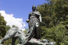 跨步在死的狮子雕塑的妇女 免版税库存图片