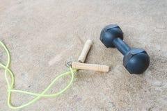 跨越横线和dumbell一锻炼的在水泥地板上 免版税库存图片