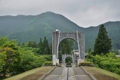 跨过在绿色山谷的步行者的庄严石桥梁在日光,日本 库存图片