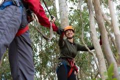 跨过邮编线的人帮助的妇女在森林里 免版税库存照片