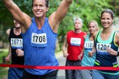 跨过终点线的马拉松男性运动员 免版税库存图片