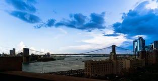 跨过East河,在浩大的蓝色傍晚天空下的布鲁克林大桥的全景在街市 库存图片