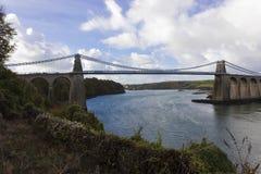 跨过Menai海峡, Anglesey小岛,北部威尔士的历史的Menai吊桥的风景看法 免版税库存照片